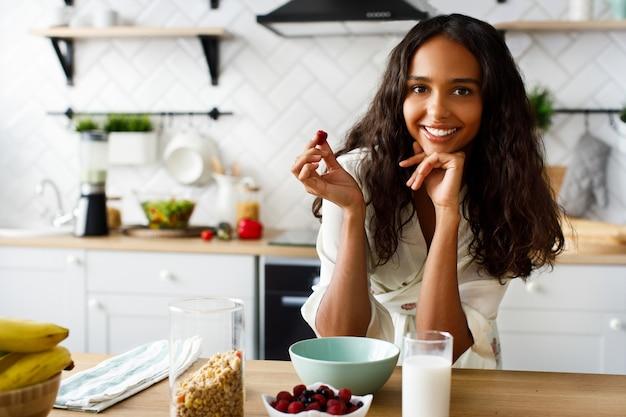 Улыбчивая привлекательная женщина-мулатка держит малину возле стола со стаканом молока и хрустит на белой современной кухне, одетая в пижаму с распущенными волосами и выглядящая прямо Бесплатные Фотографии