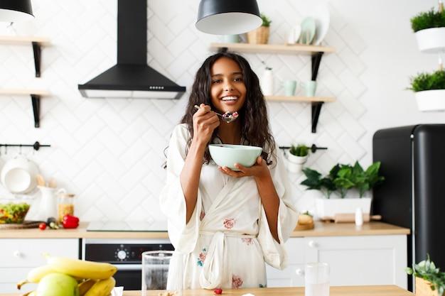 Улыбчивая привлекательная женщина-мулатка ест нарезанные фрукты на белой современной кухне, одетой в пижаму с грязными распущенными волосами и выглядящей прямо Бесплатные Фотографии