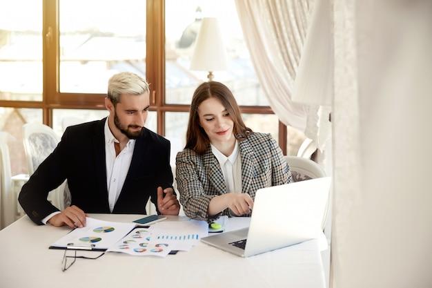 若い金髪の男とブルネットの女性はコンピューターを見て、ビジネスプランを議論しています 無料写真