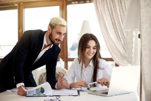 Рабочий процесс в бизнес-центре молодой брюнетки и привлекательного мужчины внутри здания, смотрящего на ноутбук Бесплатные Фотографии