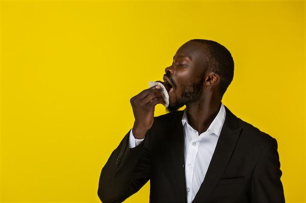 アフリカ系アメリカ人の若い男はカップケーキを食べています 無料写真