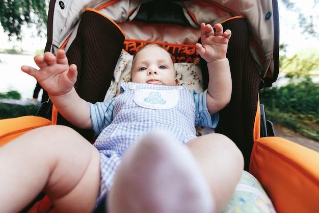 ベビーカーのスタイリッシュな服でかわいい青い目の赤ちゃん少年 無料写真
