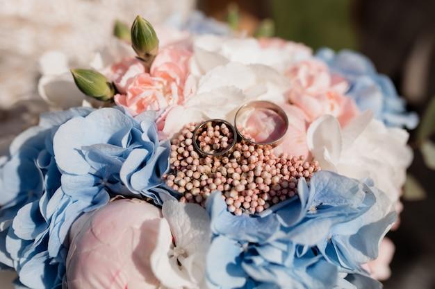 Два одинаковых обручальных кольца лежат на свадебном букете Бесплатные Фотографии