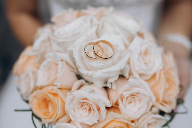 Два обручальных кольца лежат на свадебном букете Бесплатные Фотографии