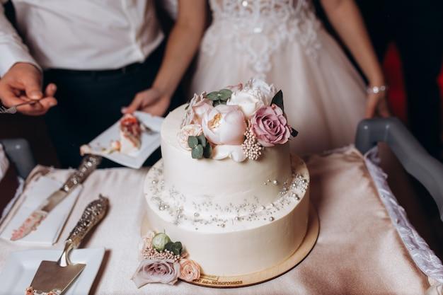 新婚夫婦はウェディングケーキを味わいます 無料写真