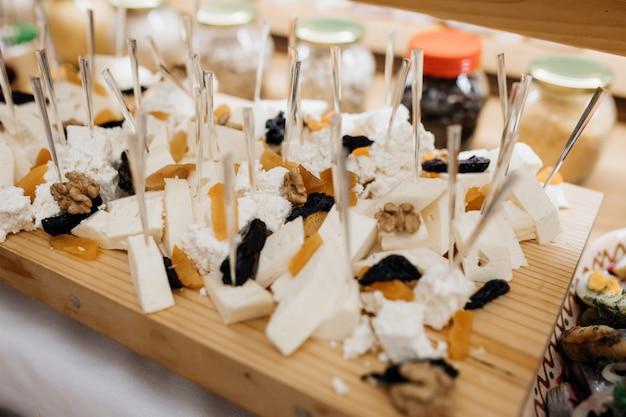 木製の机の上にチーズやドライフルーツのようなスナックがあります。 無料写真