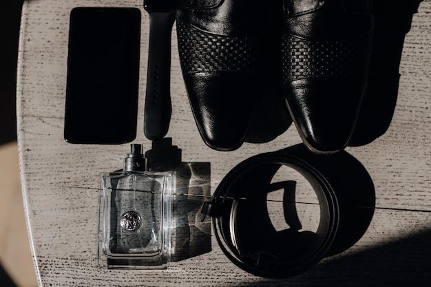 Обувь, ремень, духи и телефон на деревянной поверхности Бесплатные Фотографии