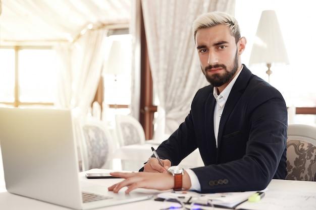 真面目な上司は真っ直ぐに見て、レストランでノートパソコンとのビジネスミーティングの準備をしています 無料写真
