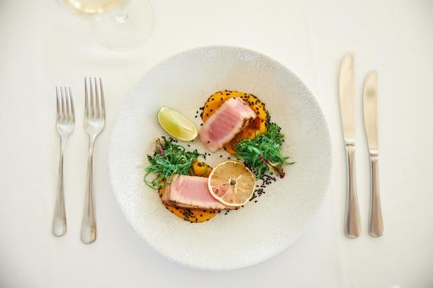 レモンスライスとソースを添えた美味しいマグロ料理 無料写真