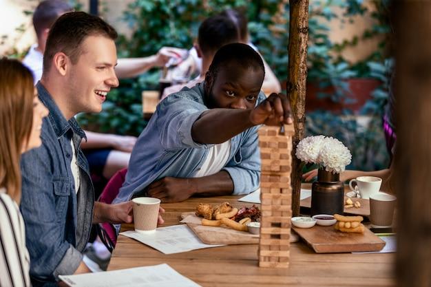 アフリカの少年は、地元の居心地の良いレストランで白人の親友とテーブルゲームジェンガをプレイしています。 無料写真