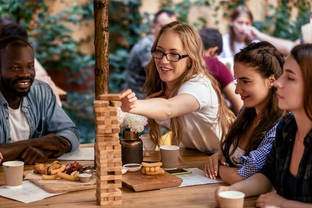 白人女性がレストランでテーブルゲームジェンガで背の高い塔にレンガを入れています 無料写真