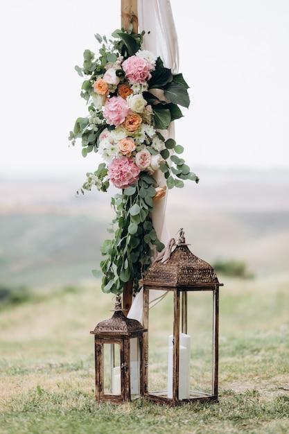 ユーカリと屋外のキャンドルで柔らかいピンクの花で作られた花の組成 無料写真