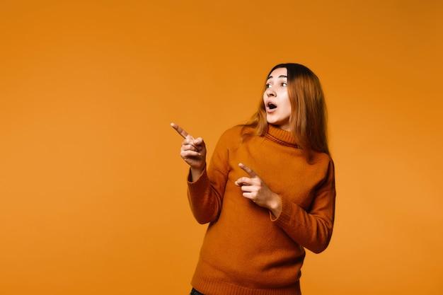 左隅に指で何かを見せて、プルオーバーに身を包んだ美しい驚いた赤毛白人女性のビュー 無料写真
