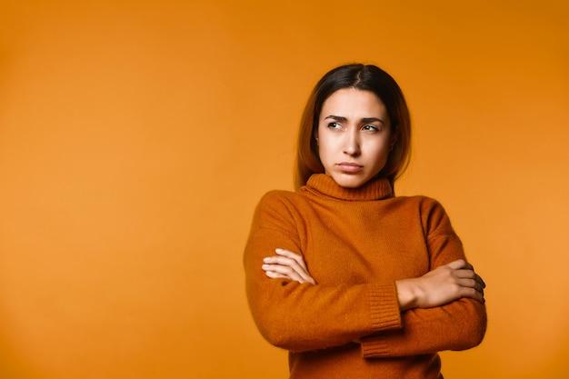 Вид вдумчивый молодой кавказской женщины, одетые в пуловер, серьезно сосредоточены Бесплатные Фотографии