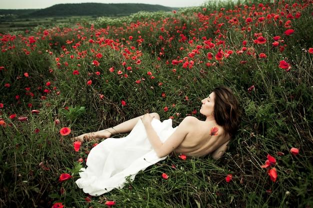 ケシの花の中で白いシャツを着た女性が裸で横たわっています 無料写真