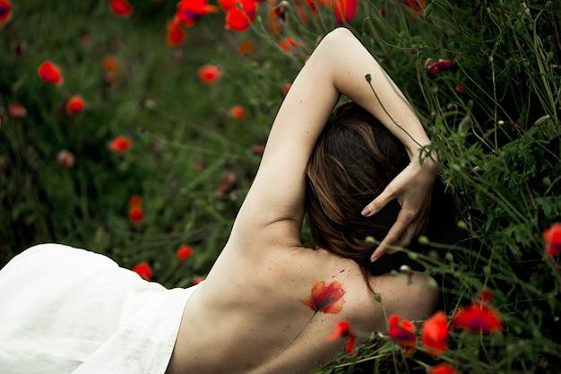 女性は裸の背中に横たわっており、入れ墨はケシの花の中で白いシャツに覆われています 無料写真