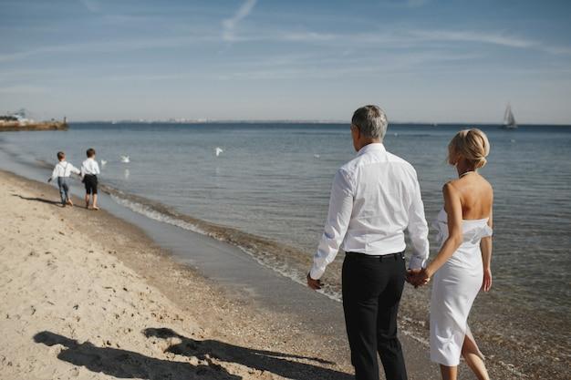 Вид сзади родителей, которые держатся за руки вместе и двух молодых сыновей перед ними на береговой линии Бесплатные Фотографии