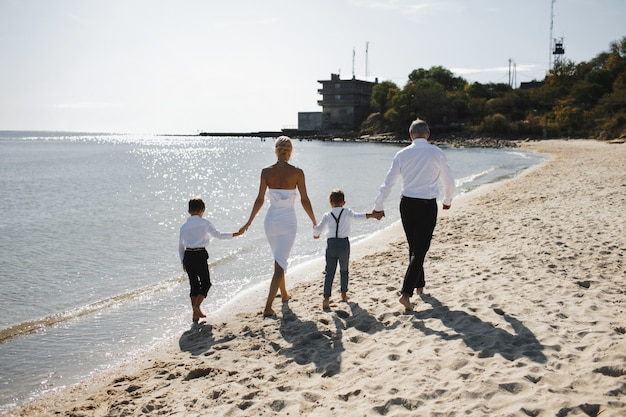 Вид сзади, родители и дети держатся за руки и гуляют по пляжу в солнечный летний день, одетые в белую стильную одежду Бесплатные Фотографии