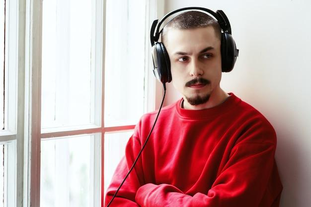Человек скрещивает руки, слушая музыку на подоконнике Бесплатные Фотографии