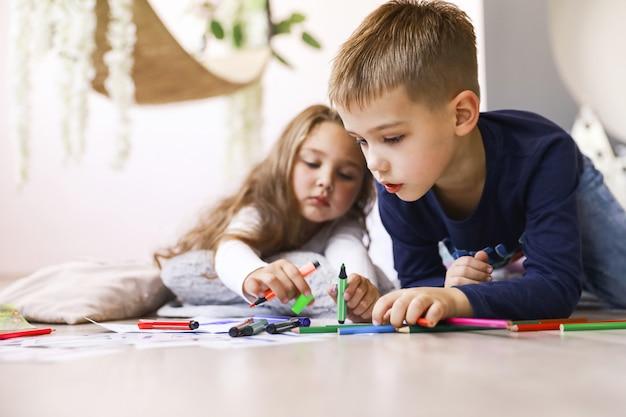 Братья и сестры держат яркие карандаши и рисуют на полу Бесплатные Фотографии