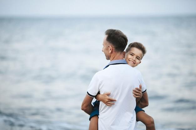 Папа держит сына на руках, а ребенок смотрит прямо и улыбается на берегу моря. Бесплатные Фотографии