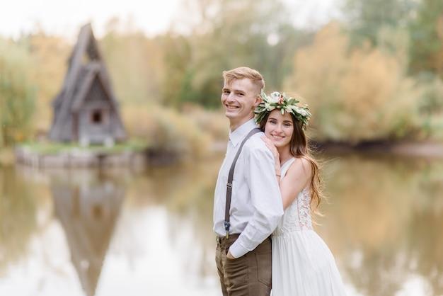 Улыбающаяся влюбленная пара обнимается возле небольшого озера, одетая в уютный свадебный наряд в осеннем парке Бесплатные Фотографии