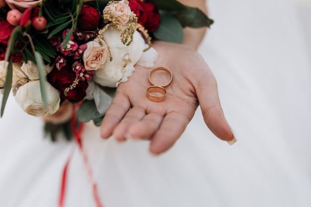 Обручальные кольца на руку женщине, свадебный букет из красных и белых цветов, детали свадьбы Бесплатные Фотографии