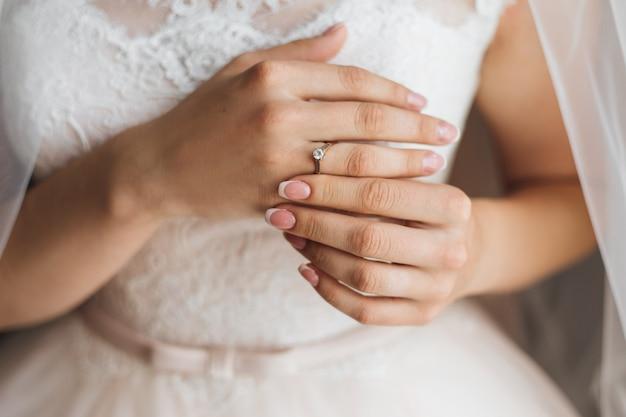 Руки невесты с нежным французским маникюром и драгоценным обручальным кольцом с блестящим бриллиантом, свадебное платье Бесплатные Фотографии