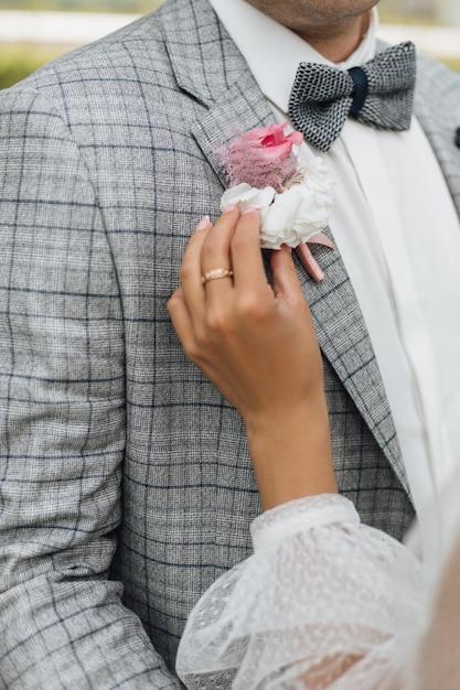 花嫁は新郎のジャケットにブートニアを顔なしで抱きしめます 無料写真