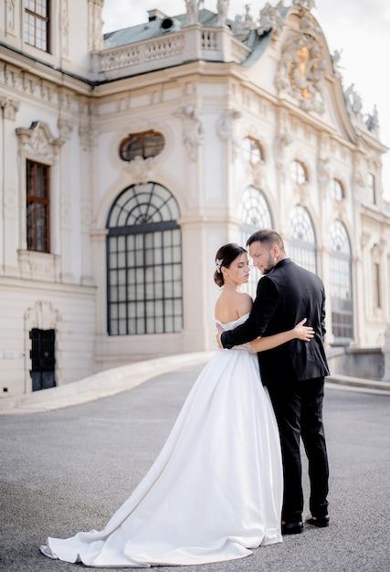 愛の美しい結婚式のカップルは歴史的な建築物の前に一緒に立っています。 無料写真