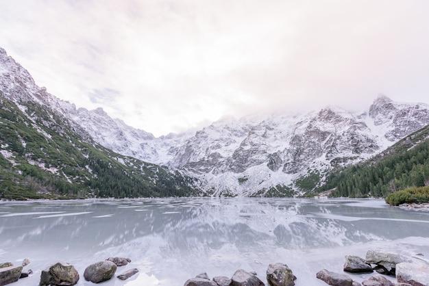 Захватывающий вид зимних снежных гор и замерзшего высокогорного озера Бесплатные Фотографии