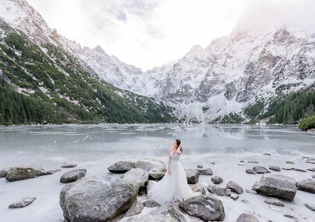 雪に覆われた山々に囲まれた凍った湖の前に白いドレスの魅力的な女の子が立っています。 無料写真