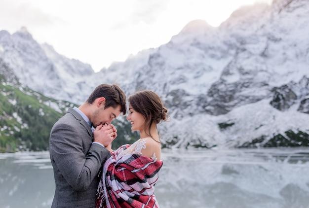 Замерзшая свадебная пара прогревается вместе в зимних горах перед замерзшим озером Бесплатные Фотографии