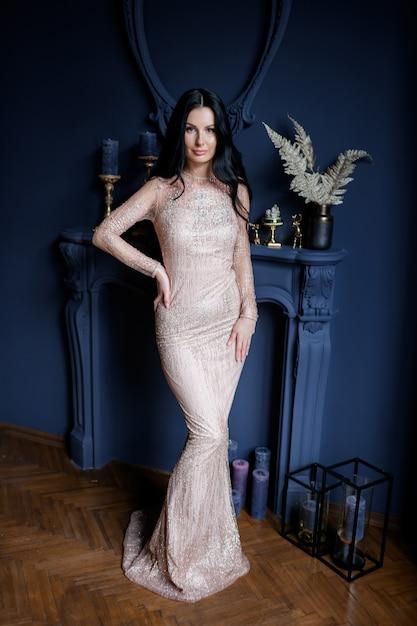 魅力的な若い女の子は暖炉のある青い背景に贅沢な長いベージュのドレスで立っています。 無料写真