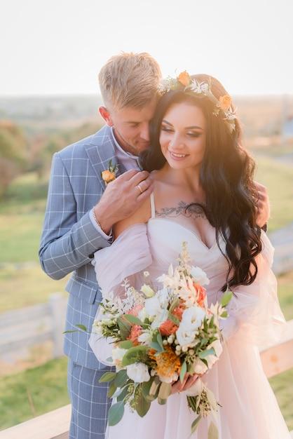 美しい結婚式のブーケと晴れた日に花輪を捧げる草原で屋外の愛の微笑む優しい結婚式のカップル 無料写真