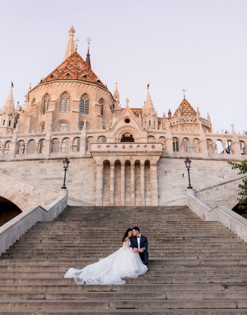暖かい夜に古い石造りの歴史的な建物の階段に優しい結婚式のカップルが座っています。 無料写真