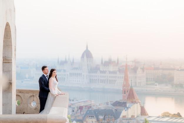 ブダペストの素晴らしい景色を望む古い歴史的建造物の石造りのバルコニーでの結婚式のカップル 無料写真