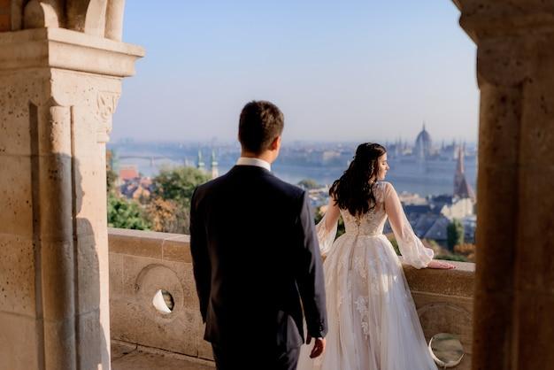 美しい町の風景と石造りの建物の上に晴れた日に結婚式のカップルの背面図 無料写真