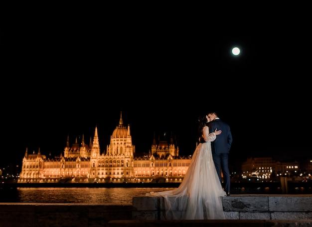 夜のブダペストで絵のように照らされた議会と恋に結婚式のカップルの背面図 無料写真