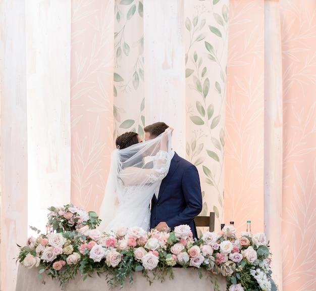 ベールで覆われた結婚式のカップルは、バラで飾られた結婚式のテーブルの横にキスをしています 無料写真