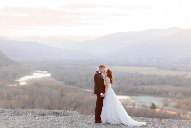 Красивая свадебная пара целуется на холме с видом на живописный пейзаж в сумерках. Бесплатные Фотографии