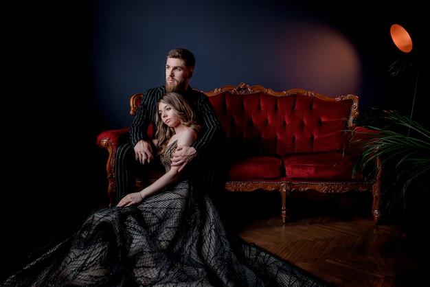 魅力的な女性はエレガントなイブニングドレスに身を包んだし、一緒に手を繋いでいると豪華な赤いソファに座っている黒のスーツに身を包んだハンサムなひげを生やした 無料写真