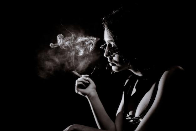 Монохромный портрет молодой девушки, которая курит с большим декольте и в очках Бесплатные Фотографии