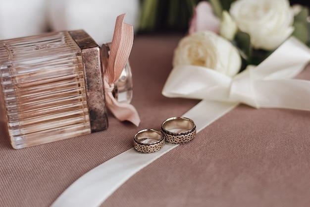 クリーミーなリボン、香水、白い花に刻印された結婚指輪 無料写真