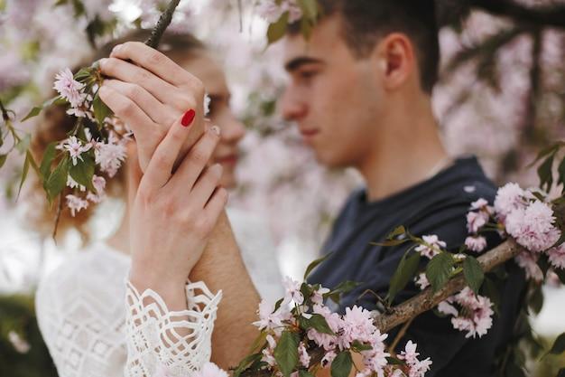 Мальчик и девочка стоят лицом к лицу под цветущим весенним деревом Бесплатные Фотографии
