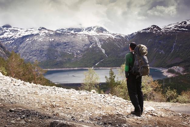 ノルウェーの山々でゴージャスな景色の前に、観光客のリュックサックを持つ男が立っています 無料写真