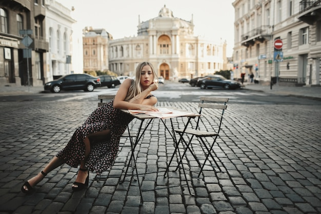女性は古い建築物に囲まれた通りのコーヒーテーブルの近くに一人で座っています。 無料写真