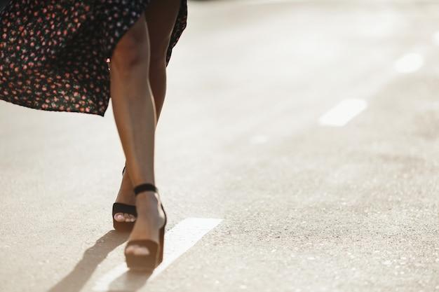 Женские ножки на высоких каблуках на дороге в солнечный день Бесплатные Фотографии