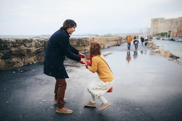 男と女は雨の中で路上で楽しんでいます 無料写真