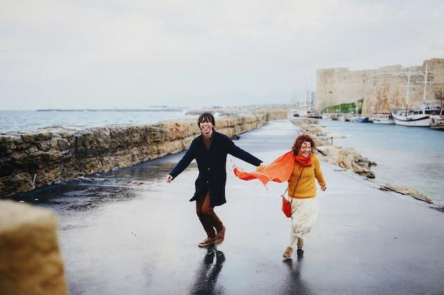 男と女は雨、空の海岸で楽しんでいます 無料写真